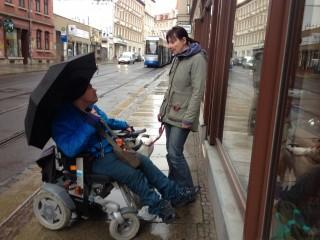 Bildinhalt: In leichter Sprache - Über einen Rundgang | nicht immer Rollstuhl gerecht. Daniela Nuß mit Besucher vor dem Laden.